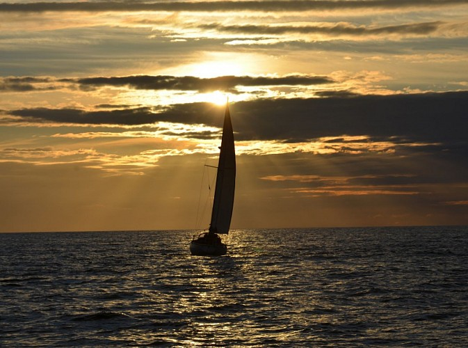 The sunset on a sailing ship off the coast of Saint-Valery-en-Caux